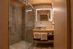 Blick ins Badezimmer mit großer, barrierefreier Glasdusche und Waschtisch mit beleuchtetem Spiegel