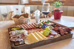 Detailaufnahme einerBrettljause mit Wurst, hausgemachtem Speck, Käse, Tomaten und Garnierung, dahinter Brotkorb und Rotwein im Glas