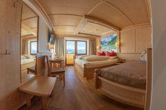 Blick ins Doppelzimmer Ahorn mit Garderobe, Zusatzbett, Doppelbett und Aussicht