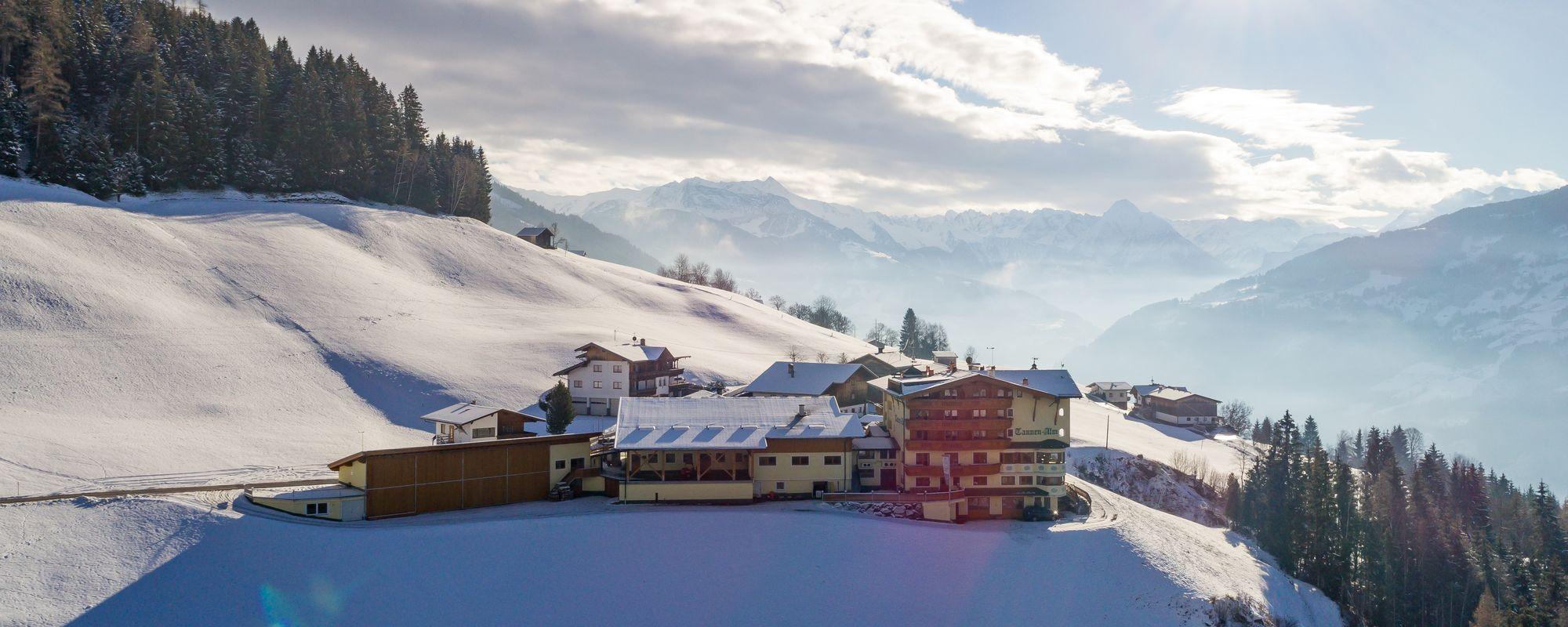 Aussenaufnahme der Tannenalm mit schneebedeckten Hängen und strahlendem Winterhimmel