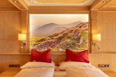 Direkter Blick auf das hinterleuchtete Wandbild am Kopfende des Bettes