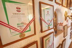 Detailaufnahme gerahmter Auszeichnungen an der Wand im Restaurant des Alpengasthof Tannenalm