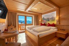 Blick über das Doppelbett Richtung Fensterfront im Doppelzimmer Ahorn an einem strahlend schönen Wintertag