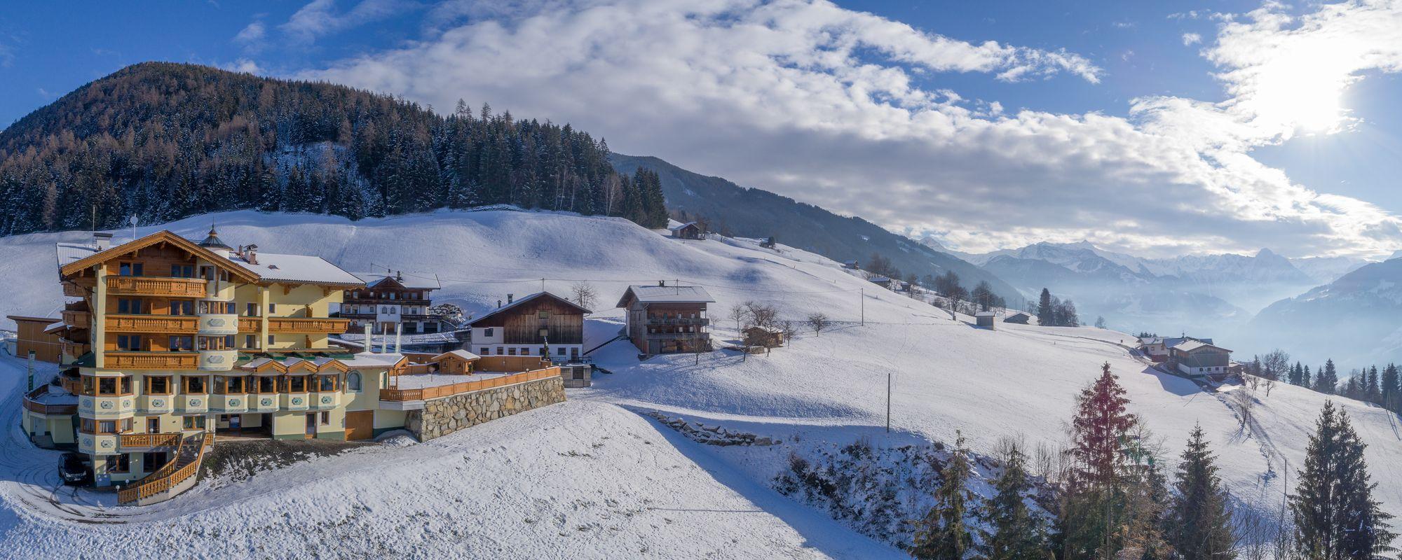 Panoramaufnahme des Alpengasthof Tannenalm an einem klaren Wintertag