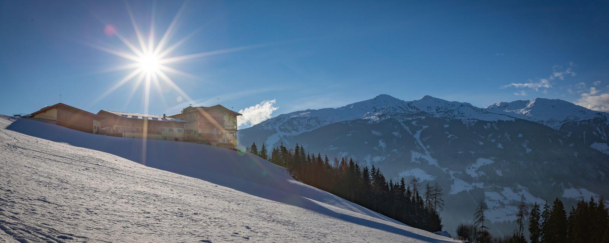 Blick hinauf zum Alpengasthof Tannenalm über schneebedecktes Feld, Sonne dahinter hoch am Himmel
