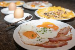Detailaufnahme von Frühstücksteller mit Wurst und Spiegeleiern, dahinter frisch gekochte Eier im Becher und Eieromelette