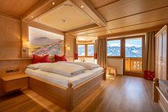 Blick auf das Doppelbett mit hinterleuchtetem Wandbild, Erker mit Sitzecke und Fensterfront